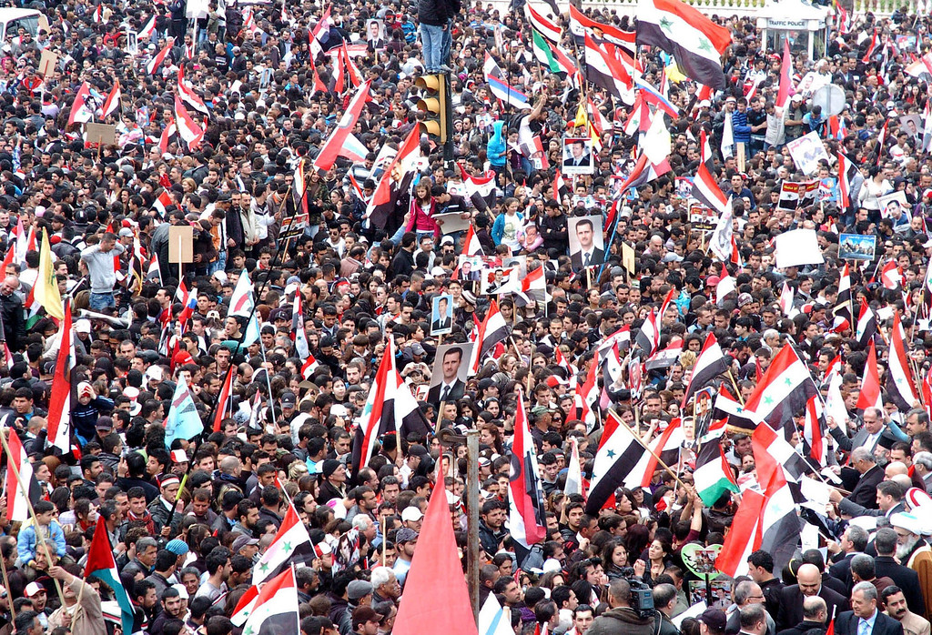 . A handout picture released by the official Syrian Arab News Agency (SANA) shows Syrians waving national flags and portraits of President Bashar al-Assad during a pro-regime rally in the coastal city of Latakia on the first anniversary of the anti-government revolt on March 15, 2012. State television showed tens of thousands of people taking to the streets in a ashow of allegiance to  the regime in main squares in the capital Damascus, the northern city of Aleppo, Latakia on the Mediterranean coast, Daraa and Suweida to the south and Hasaka in the northeast. ( -/AFP/Getty Images)