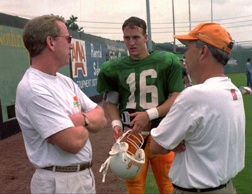 . Former pro quarterback Archie Manning, left, goes over some finer points with his son, Tennessee quarterback Peyton Manning, and Vol offensive coordinator-quarterbacks coach David Cutcliffe during practice Tuesday, Aug. 13, 1996, in Knoxville, Tenn. While both Mannings are All-American stories, Peyton\'s teammates have turned up in jail or suspended. (AP Photo/Knoxville News-Sentinel, Paul Efird)