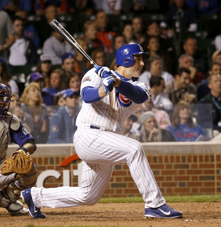 . Chicago Cubs\' Anthony Rizzo hits an RBI single off Colorado Rockies relief pitcher Chad Bettis, scoring Emilio Bonifacio, during the eighth inning of a baseball game Monday, July 28, 2014, in Chicago. The Cubs won 4-1. (AP Photo/Charles Rex Arbogast)
