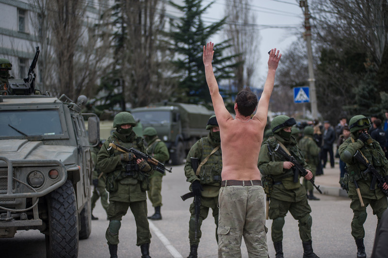 . A Ukrainian man stands in protest in front of gunmen in unmarked uniforms as they stand guard in Balaklava, on the outskirts of Sevastopol, Ukraine, Saturday, March 1, 2014. An emblem on one of the vehicles and their number plates identify them as belonging to the Russian military. Ukrainian officials have accused Russia of sending new troops into Crimea, a strategic Russia-speaking region that hosts a major Russian navy base. The Kremlin hasn�t responded to the accusations, but Russian lawmakers urged Putin to act to protect Russians in Crimea. (AP Photo/Andrew Lubimov)