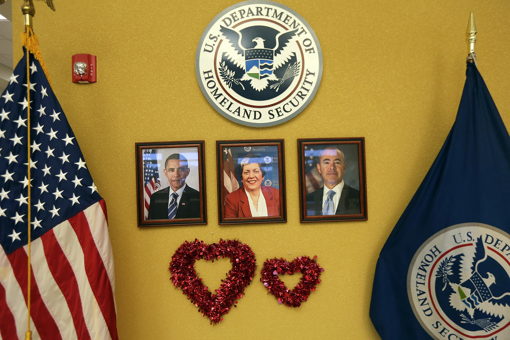 . Portraits of U.S. President Barack Obama, U.S. Homeland Security Secretary Janet Napolitano and Alejandro Mayorkas, Director of U.S. Citizenship and Immigration Services, (USCIS), are adorned with hearts at a special Valentine\'s Day naturalization ceremony for married couples on February 14, 2013 in Tampa, Florida. The U.S. Citizenship and Immigration Service (USCIS) held the Valentine\'s Day ceremony in Tampa for 28 married couples from 15 different countries.  (Photo by John Moore/Getty Images)