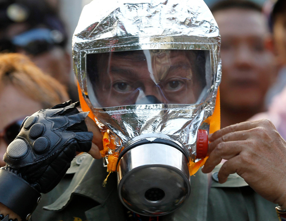 . A Thai anti-government protester wears a gas mask at a protest site near Government House in Bangkok, Thailand, 18 February 2014.  EPA/RUNGROJ YONGRIT