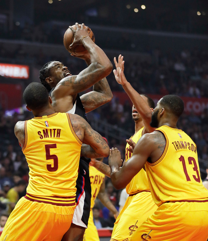 . Los Angeles Clippers\' DeAndre Jordan, top left, looks to shoot against defense by Cleveland Cavaliers\' J.R. Smith, and Tristan Thompson during the first half of an NBA basketball game Saturday, March 18, 2017, in Los Angeles. (AP Photo/Jae C. Hong)