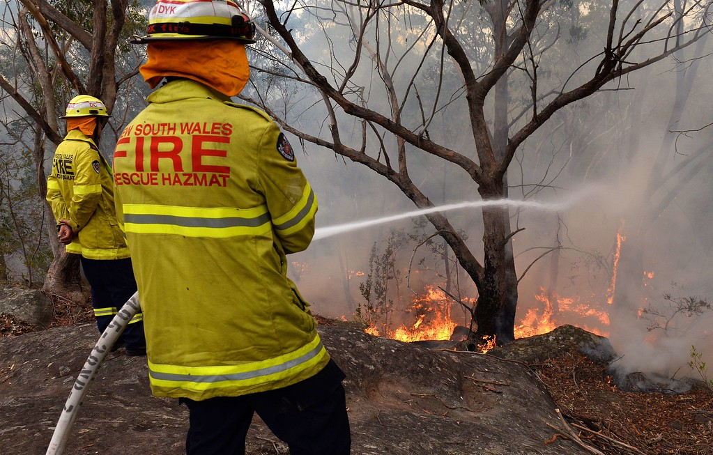 . A firefighter hoses down the flames in a backburn at Faulconbridge in the Blue Mountains on October 22, 2013.  AFP PHOTO/William WEST/AFP/Getty Images