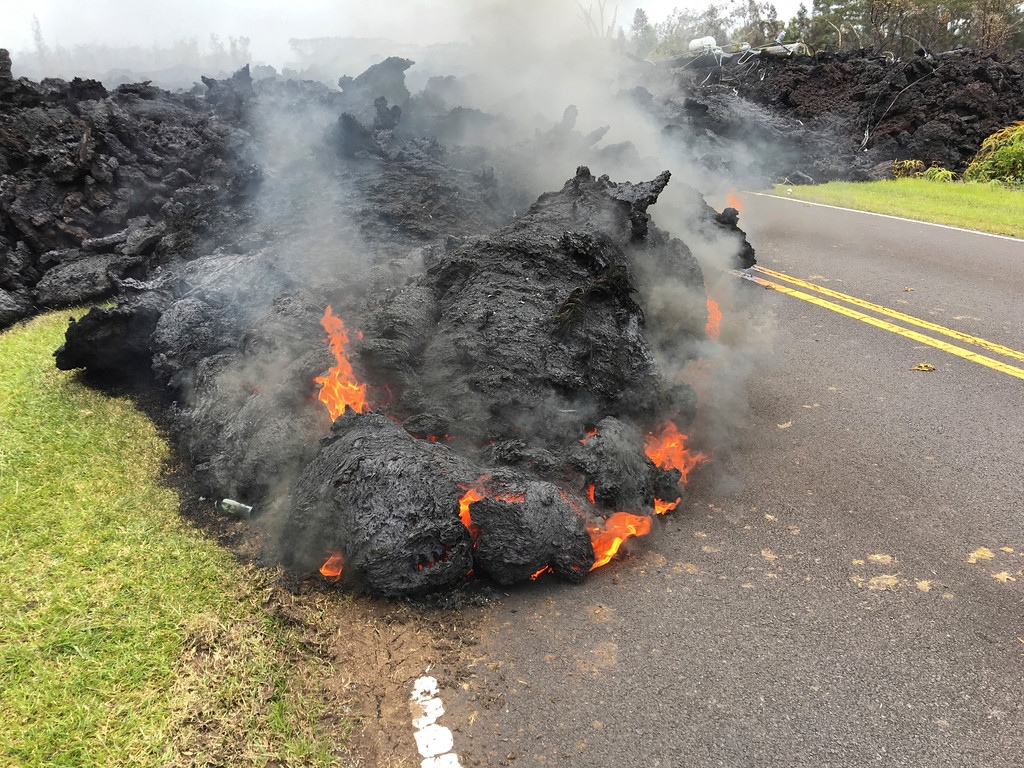 . Lava from the Kilauea volcano moves across the road in the Leilani Estates in Pahoa, Hawaii, Saturday, May 5, 2018. Hundreds of anxious residents on the Big Island of Hawaii hunkered down Saturday for what could be weeks or months of upheaval as the dangers from an erupting Kilauea volcano continued to grow. (AP Photo/Marco Garcia)