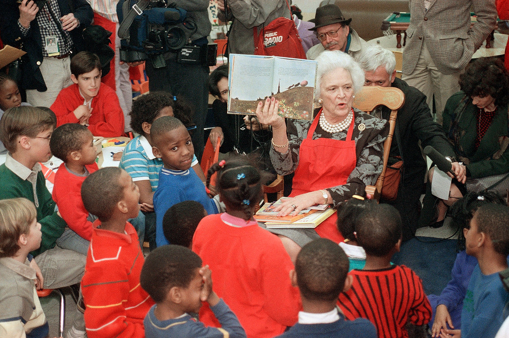 . U.S. First lady Barbara Bush reads a story to children at Martha\'s Table Day Care Center, a nonprofit center which also feeds the homeless, Tuesday, Jan. 31, 1989 in Washington. Teaching children to read is one of Mrs. Bush\'s projects. (AP Photo/Bob Daugherty)