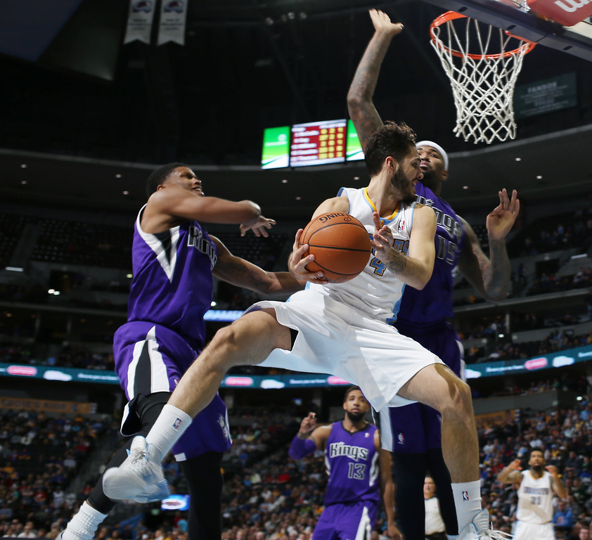 . Denver Nuggets guard Evan Fournier, front, of France, drives for a shot as Sacramento Kings forward Rudy Gay, back left, and center DeMarcus Cousins cover in the fourth quarter of an NBA basketball game in Denver, Sunday, Feb. 23, 2014.  The Kings won 109-95. (AP Photo/David Zalubowski)