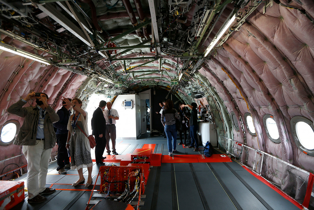 . Visitors look inside an unfitted Airbus A350 XWB as it stands on display during Farnborough International Air Show, Farnborough, England, Monday, July 14, 2014. (AP Photo/Sang Tan)