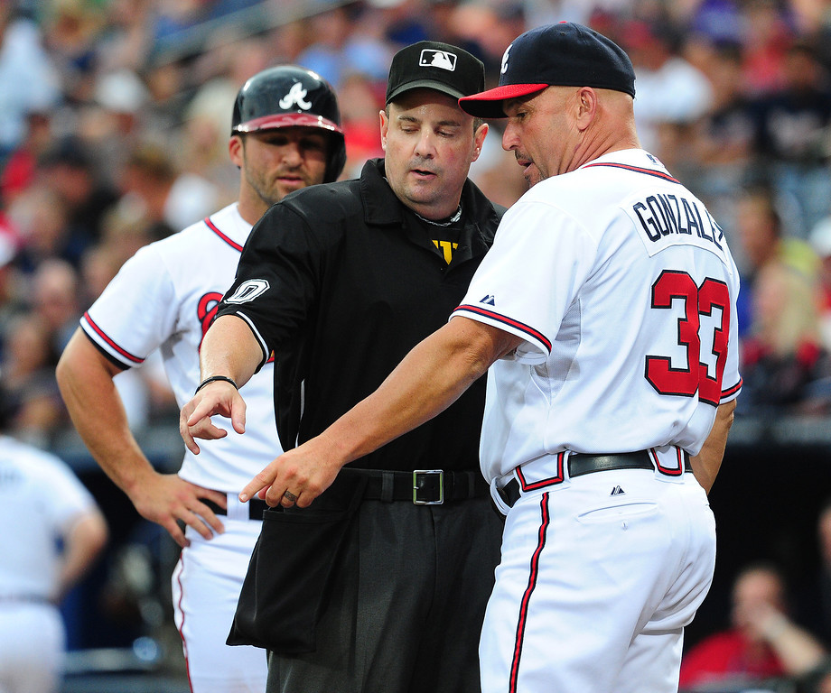 . Manager Fredi Gonzalez #33 of the Atlanta Braves disputes a call with Umpire Marty Foster as Dan Uggla watches on during the game against the Colorado Rockies at Turner Field on July 31, 2013 in Atlanta, Georgia. (Photo by Scott Cunningham/Getty Images)