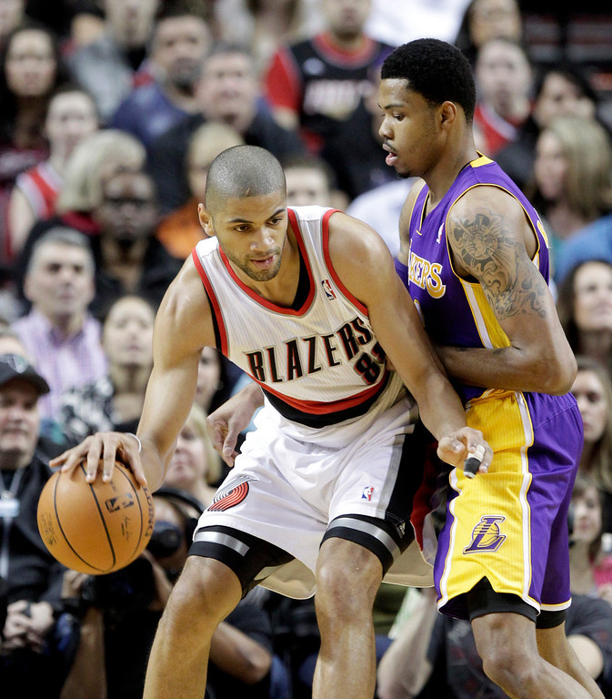 . Portland Trail Blazers forward Nicolas Batum, left, of France, maneuvers against Los Angeles Lakers guard Kent Bazemore during the first half of an NBA basketball game in Portland, Ore., Monday, March 3, 2014. (AP Photo/Don Ryan)