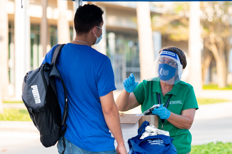 Sandra Stokes (right) assists a student with picking up their mask on the first day of the 2020 fall semester.