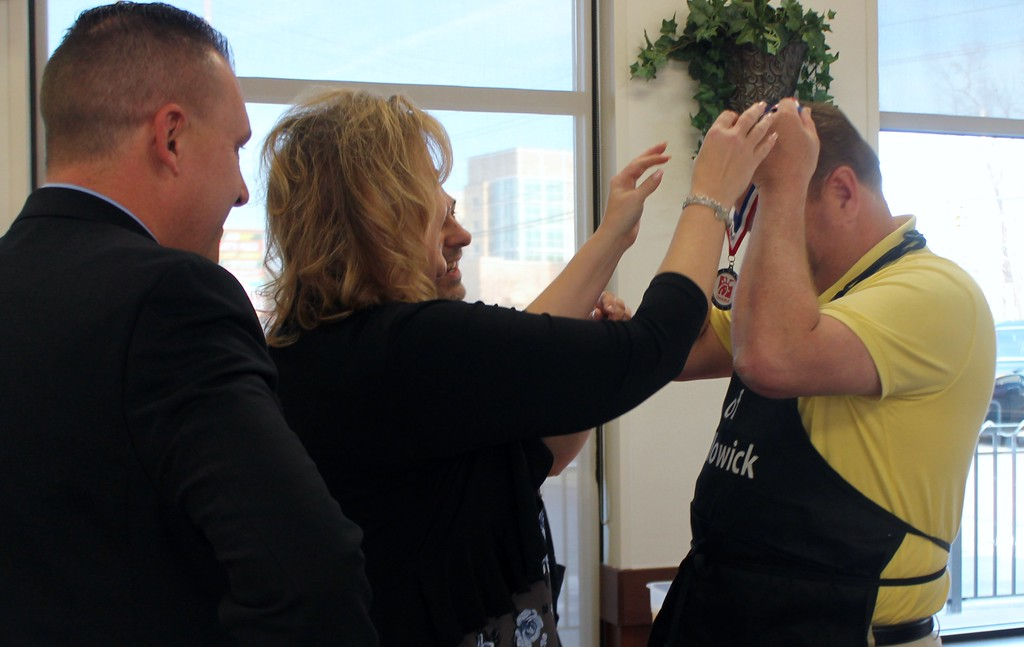 . Kristi Garabrandt � The News-Herald <br> George Phillips, announcer for Lake County Captains, watches as Eastlake Mayor Dennis Morley assists Chick Fil-A Willoughby owner, Billie Federer, in presenting Willowick Mayor Rich Regovich a participation medal after the lemon squeeze competition.