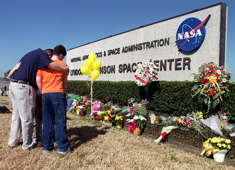 . Adam Cole and his children Kate,10, back, and Kurth,12, embrace while looking at flowers placed at the sign outside the Johnson Space Center in Houston, in honor of the crew of the space shuttle Columbia Saturday, Feb. 1, 2003. The shuttle broke apart over Texas, killing all seven astronauts, minutes before their scheduled landing in Florida. (AP Photo/Houston Chronicle, D. Fahleson)