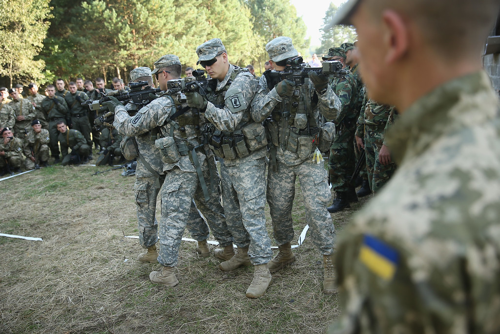 ". Members of the U.S. Army 173rd Airborne Brigade demonstrate urban warfare techniques as Ukrainian soldiers look on on the second day of the ""Rapid Trident\"" NATO military exercises on September 16, 2014 near Yavorov, Ukraine. (Photo by Sean Gallup/Getty Images)"