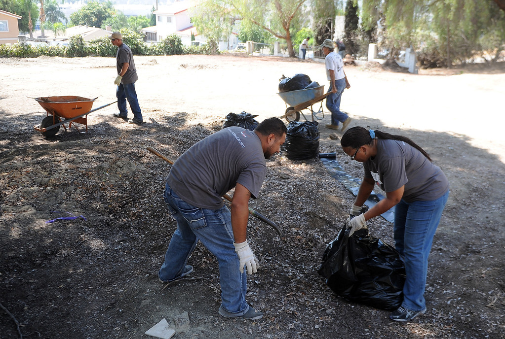 . Volunteer\'s Albert Cejas, left, shovels dirt and debris as Peggy Peppers begs the debris as Pomona Valley Habitat for Humanity and Verizon employees work to clear an area where a home will be built for a veteran on Wednesday, Aug. 14, 2013 in Walnut, Calif.   (Keith Birmingham/Pasadena Star-News)
