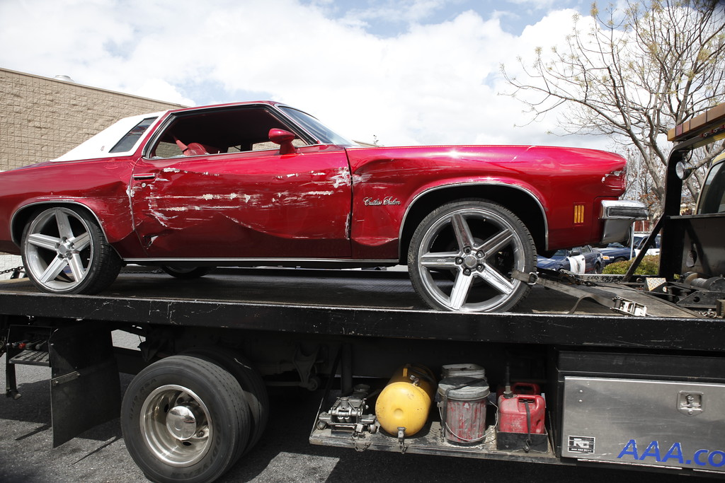 . A red Cutlass Salon is towed away after crashing into a Walmart store on Story Road in San Jose, Calif., Sunday afternoon, March 31, 2013.  (Karl Mondon/Staff)