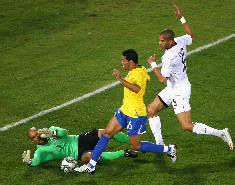 . Andre Santos of Brazil (C) in action against Tim Howard of the USA and Oguchi Onyewu of the USA (R) during the FIFA Confederations Cup match between USA and Brazil at Loftus Versfeld Stadium on June 18, 2009 in Pretoria, South Africa.  (Photo by Christof Koepsel/Bongarts/Getty Images)