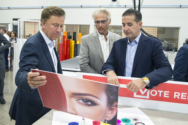 """09/09/19  Wesley Bunnell   Staff  Gov. Ned Lamont, L, speaks with Executive Director of Sign Pro Ron Bucchi, middle, and President Peter Rappoccio on a tour of the facility on Monday afternoon. Gov. Lamont visited Sign Pro on a visit to discuss Proposed Bill No. 5504 """"An Act Concerning the Net Economic Value of State contracts"""". The bill recommends the state hire CT businesses on contracts using state funding as part of the state contracting practices."""