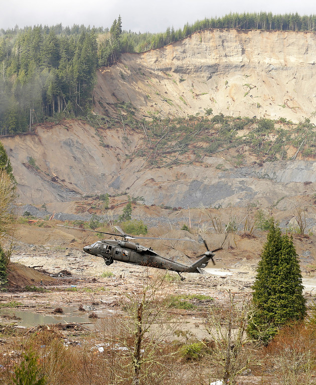 . A military helicopter flies Thursday, March 27, 2014, over mud and debris from the massive mudslide that struck Saturday near Darrington, Wash. Search and recovery work continued throughout the day. (AP Photo/Ted S. Warren, Pool)