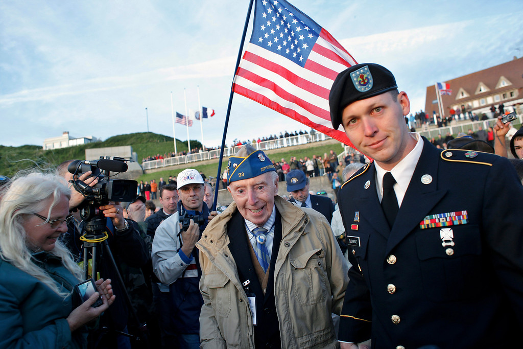 . World War II veteran of the U.S. army 29th Infantry Division, Don McCarthy, 90, from Rhode Island, center, arrives for a D-Day commemoration, on Omaha Beach, western France, Friday June 6, 2014. Veterans and Normandy residents are paying tribute to the thousands who gave their lives in the D-Day invasion of Nazi-occupied France 70 years ago.  (AP Photo/Thibault Camus)
