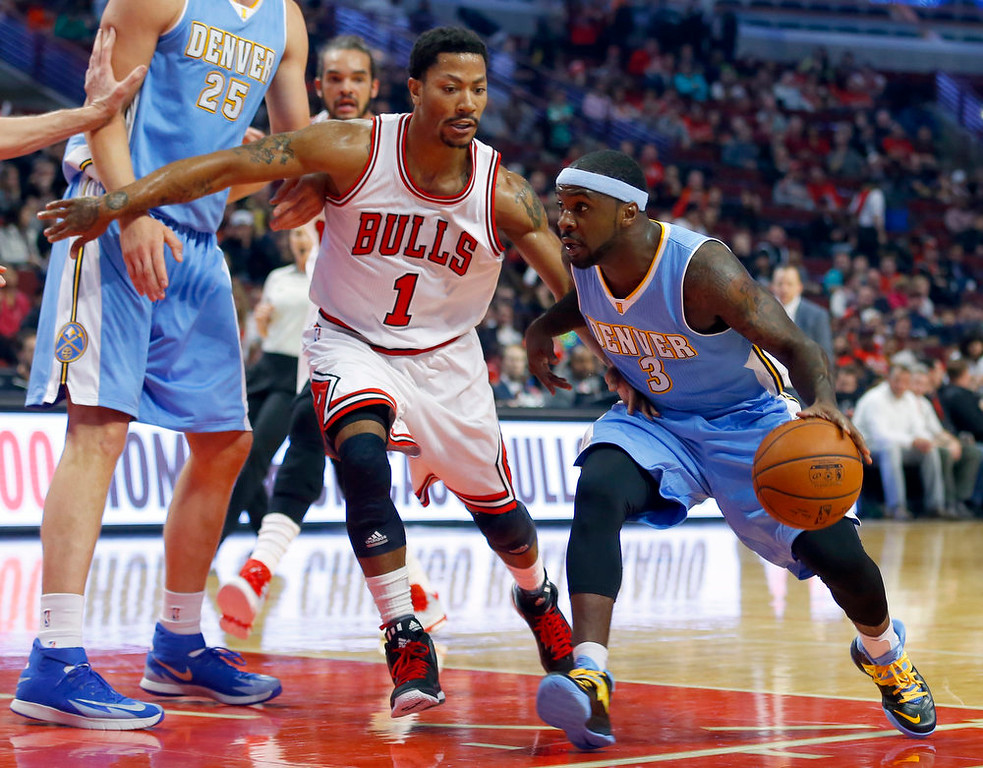 . Chicago Bulls guard Derrick Rose (1) guards Denver Nuggets guard Ty Lawson (3) during the first half of a pre-season NBA basketball game in Chicago, on Monday Oct. 13, 2014. (AP Photo/Jeff Haynes)