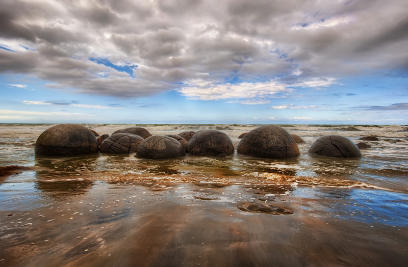 """The Mysterious Moeraki Boulders These are some of the most mysterious and alien structures I have ever seen! Yesterday I remarked that I had a major in computer science.  Well, for a short time, I had a double-major in comp sci and Geophysics.  I got pretty deep into it until I had a fight with a Geology teacher over an intellectual matter (he was wrong and still is), and I dropped that half of the major.  Anyway, it never dulled my interest in rocks and Earth science.  So, when I saw these strange round rocks for the first time, I was extra-fascinated.  Not that I had any idea what they were.  My years of geology training did me no good at all...  I think it was even more frustrating because I knew all the things they could not be.  The remaining possibilities just seemed off-the-chart impossible.And worse, I didn't have a mobile connection to Wikipedia to help me figure it all out with my iPhone-tricorder! After I got back, I was able to figure out a bit more of the arcane science around it all.  Even more interesting, I read that 12 miles south of this spot is another are called the """"Katki Boulders"""".  They contain the bones of mosasaurs and plesiosaurs.  Cool!- Trey RatcliffClick here to read the rest of this post at the Stuck in Customs blog."""