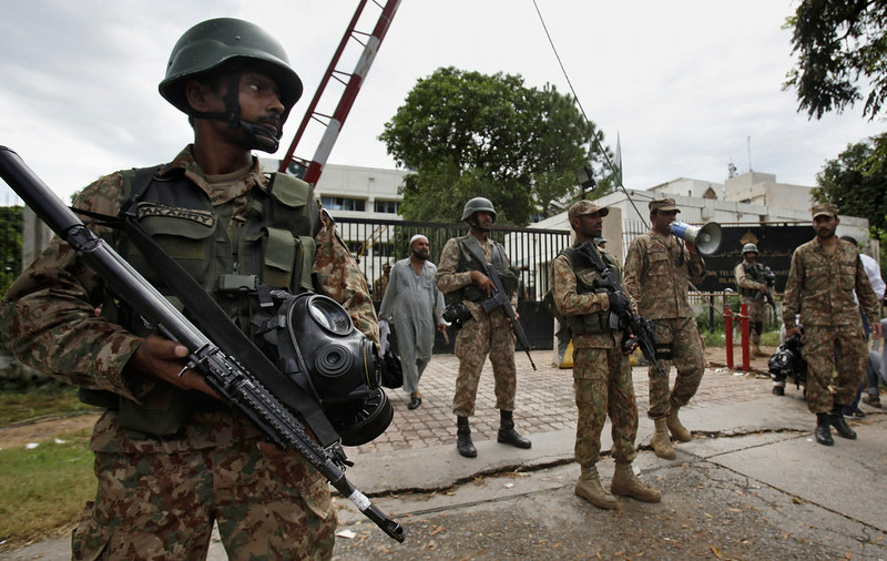 . Pakistani army troops stand guard at the main entry gate of the state television building which was occupied by protesters in Islamabad, Pakistan on Monday, Sept. 1, 2014. Anti-government protesters and Pakistani police have clashed once again as the demonstrators pushed into a sprawling government complex in the country\'s capital in an effort to try to reach the prime minister\'s official residence. (AP Photo/Anjum Naveed)
