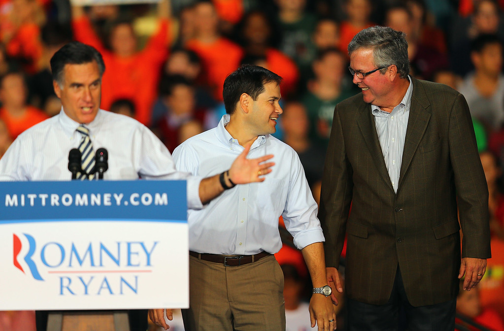 . Republican presidential candidate, former Massachusetts Gov. Mitt Romney speaks as Sen. Marco Rubio (R-FL) (C) and former Florida Gov. Jeb Bush stand next to him during a campaign rally at the BankUnited Center on the campus of the University of Miami on October 31, 2012 in Miami, Florida.  (Photo by Joe Raedle/Getty Images)