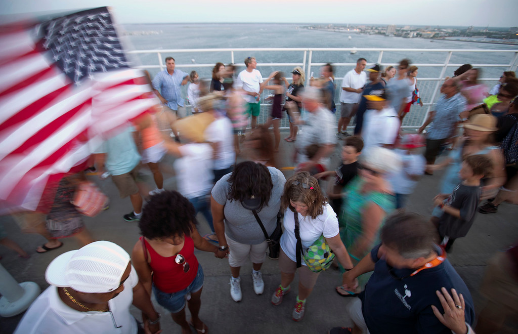 . People join hands in prayer as thousands of marchers meet on Charleston\'s main bridge in a show of unity after nine black church parishioners were gunned down during a Bible study, Sunday, June 21, 2015, in Charleston, S.C. (AP Photo/David Goldman)