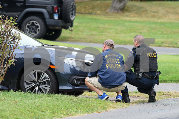 09/21/17 Wesley Bunnell | Staff A state police officer & a West Hartford police officer crouch near the intersection of Fisk & Lloyd St in Newington on Thursday morning due to a police standoff on nearby Gilbert Rd.