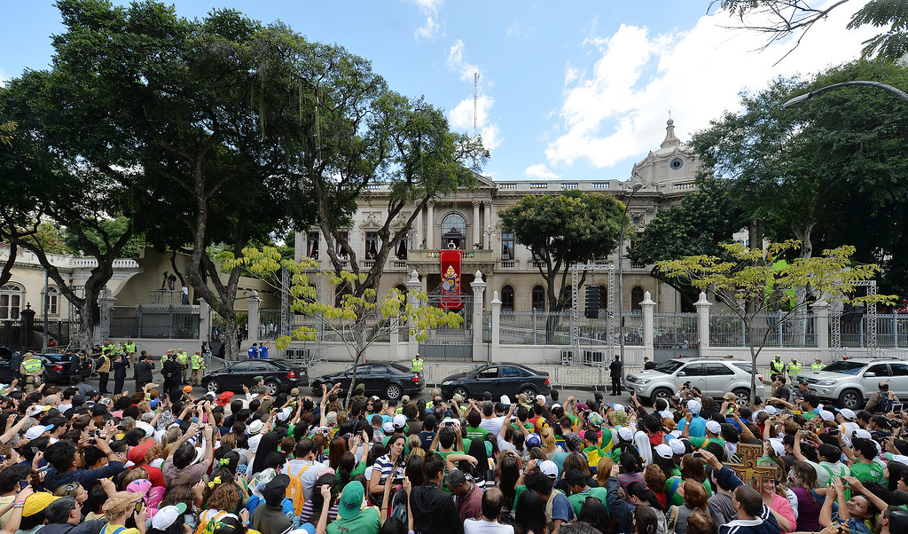 . People gather to listen to Pope Francis, top center above red banner, give Angelus noon prayer from Sao Joaquim Palace in Rio de Janeiro, Brazil, Friday, July 26, 2013. Pope Francis is on the fifth day of his trip to Brazil where he will attend the 2013 World Youth Day in Rio. (AP Photo/Luca Zennaro, Pool)