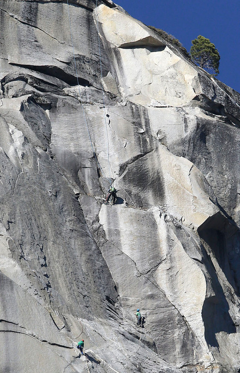 """. Tommy Caldwell, lower left, and Kevin Jorgeson, lower right, near the summit of El Capitan Wednesday, Jan. 14, 2015, as seen from the valley floor in Yosemite National Park, Calif. The two climbers vying to become the first in the world to use only their hands and feet to scale a sheer granite face in California\'s Yosemite National Park are almost to the top. Jorgeson and Caldwell have been attempting what many thought impossible. The men have been \""""free-climbing\"""" to the 3,000-foot summit for 17 days, meaning they don\'t use climbing aids other than ropes only to prevent deadly falls. Each trained for more than five years, and they have battled bloodied fingers and unseasonably warm weather. (AP Photo/Ben Margot)"""