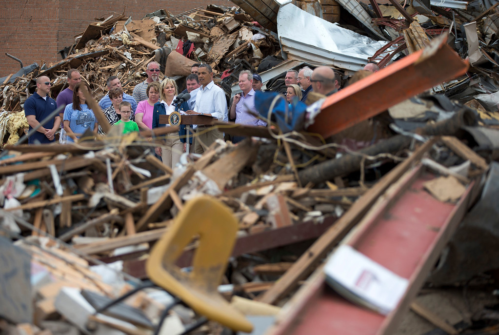 . President Barack Obama is surrounded by the rubble of the Plaza Towers Elementary School as he speaks to media in the company of school and state officials Sunday, May 26, 2013, in Moore, Okla., which was devastated by a massive tornado and severe weather last week.  (AP Photo/Carolyn Kaster)