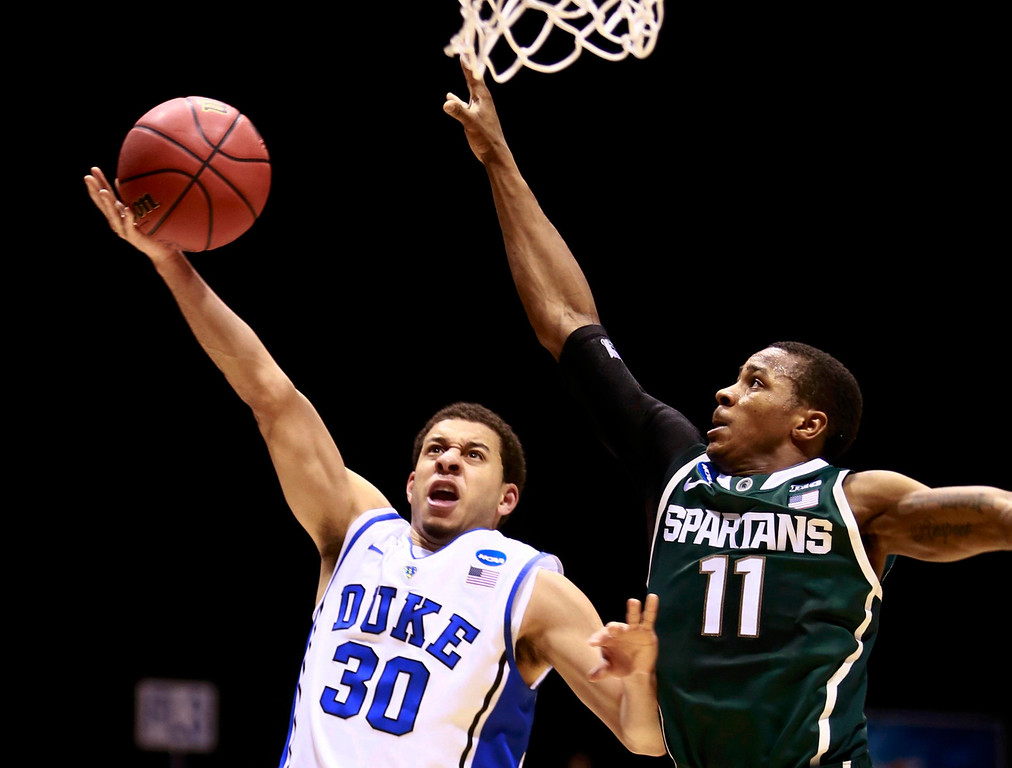 . Duke Blue Devils guard Seth Curry (30) goes to the basket against Michigan State Spartans guard Keith Appling (11) during their Midwest Regional NCAA men\'s basketball game in Indianapolis, Indiana, March 29, 2013. REUTERS/Brent Smith