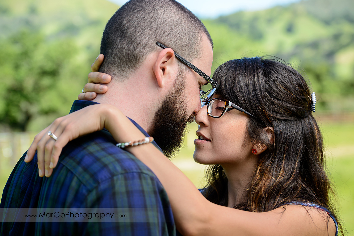 close-up portrait of woman in blue dress and man in blue shirt touching noses during engagement session at Sunol Regional Wilderness