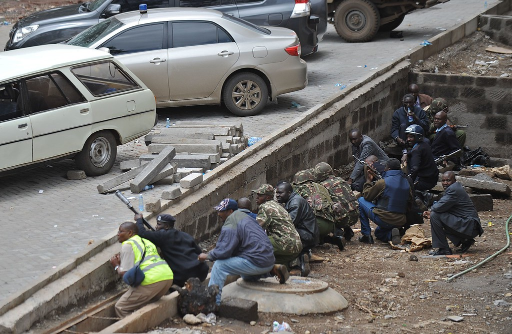 . Kenyan security personnel, crouched behind a ledge, watch on September 23, 2013 a column of smoke rise from the besieged Westgate shopping mall in Nairobi following a loud explosion.          AFP PHOTO / TONY  KARUMBA/AFP/Getty Images