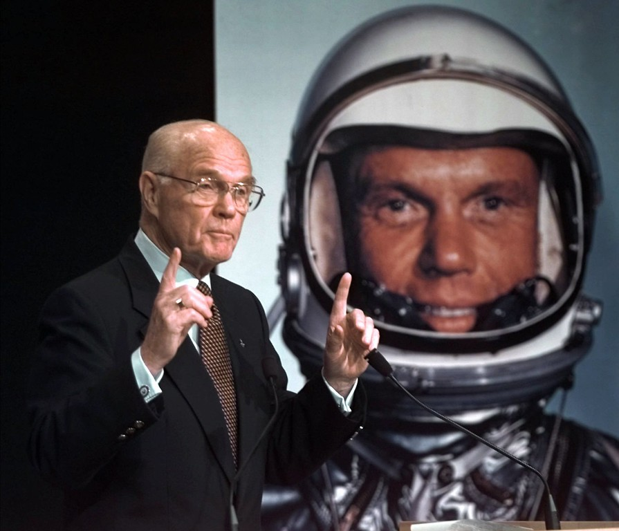 . Alongside a photo of his earlier space mission, Sen. John Glenn, D-Ohio, gestures during a news conference at NASA headquarters in Washington Friday, Jan. 16, 1998, where it was announced that NASA would rocket Glenn, 76, back into space. Glenn, who became the first American to orit the Earth 36 years ago, is tentatively set to fly on the shuttle Discovery in October. (AP Photo/Ron Edmonds)