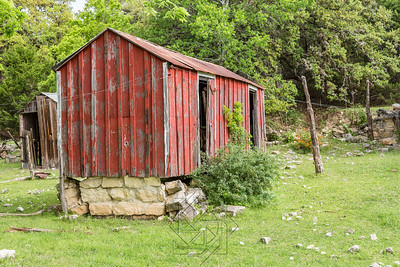 Abandoned red shack with brown shack in background