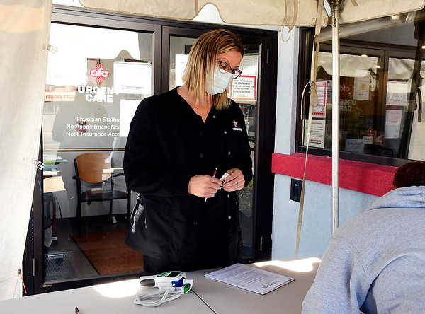4/7/2020 Mike Orazzi | Staff AFC Urgent Care's Crystal Yeske checks in a patient at the East Main Street location in New Britain on Tuesday.