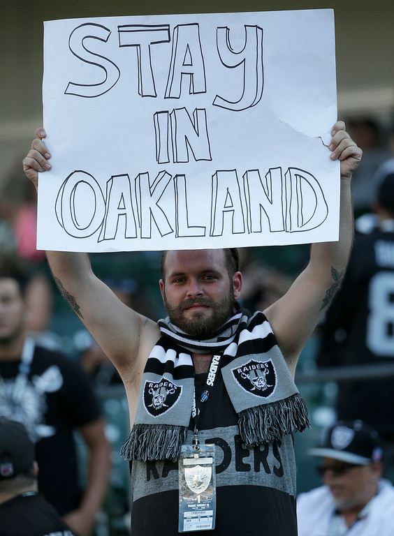 . An Oakland Raiders fan holds up a sign during an NFL preseason football game between the Raiders and the Detroit Lions in Oakland, Calif., Friday, Aug. 15, 2014. (AP Photo/Marcio Jose Sanchez)