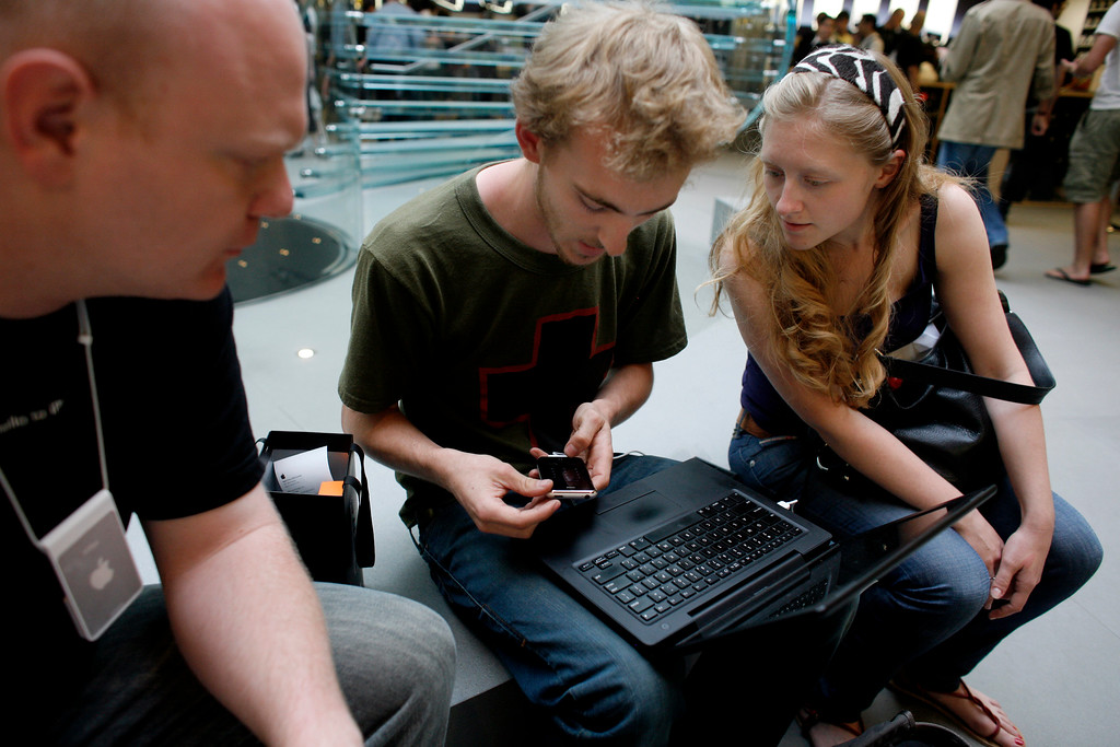 . Apple employee Mike Heigl, left, and Sarah Hawkey, right, of New York, look on as Brett Moen, also of New York, uses his laptop to activate his new iPhone inside the Apple Store, Friday, June 29, 2007 in New York.  (AP Photo/Jason DeCrow)