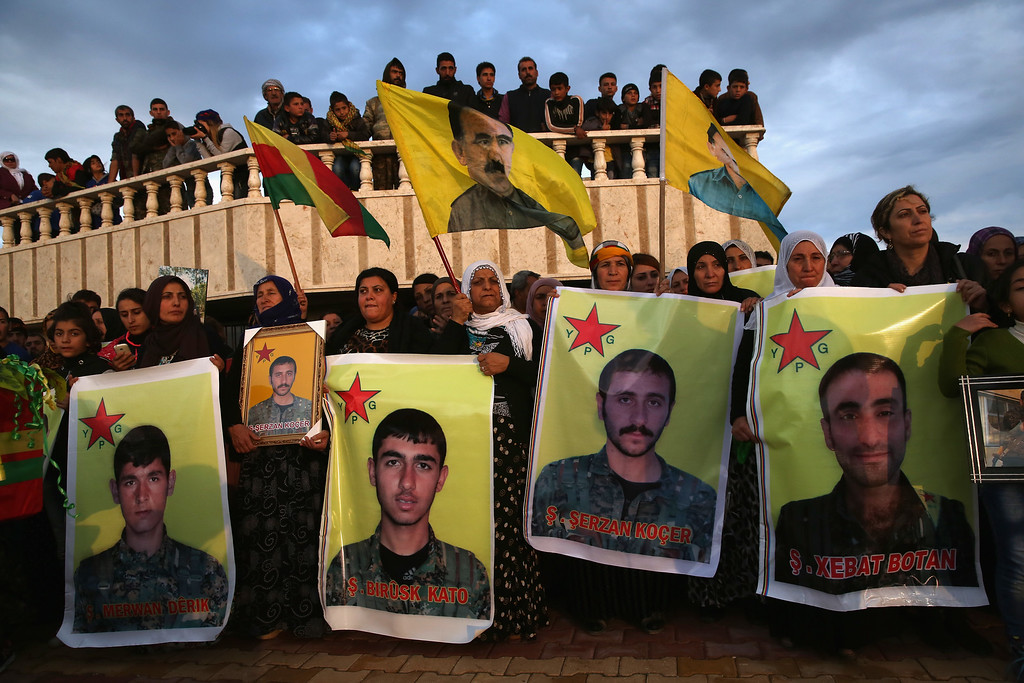 . Family members and comrades attend the funeral of eight members of the People\'s Protection Units (YPG), that were buried in a martyrs\' cemetery on November 8, 2015 in Derek, Rojava, Syria. The YPG has ties to the Kurdish Workers\' Party (PKK), and reveres PKK founder Abdullah Ocalan, seen on flag in background.  Seven of the eight were killed in an ISIL car bomb attack during an ongoing YPG offensive near Hassaka. The predominantly Kurdish region of Rojava in northeast Syria has become a bulwark against the Islamic State. Their armed forces, with the aid of U.S. airstrikes and weapons, have been battling ISIL, pushing them south towards the extremists\' stronghold of Raqqa.  (Photo by John Moore/Getty Images)