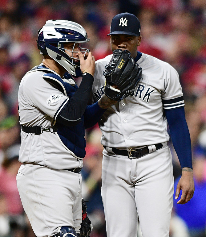 . New York Yankees catcher Gary Sanchez, left, talks with relief pitcher Aroldis Chapman during the eighth inning against the Cleveland Indians in Game 5 of a baseball American League Division Series, Wednesday, Oct. 11, 2017, in Cleveland. (AP Photo/David Dermer)