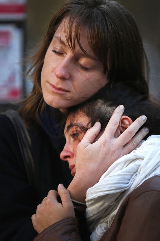 . People react as they view tributes and flowers outside La Belle Equipe restaurant on Rue de Charonne following Fridays terrorist attack and France observes three days of national mourning on November 15, 2015 in Paris, France. As France observes three days of national mourning members of the public continue to pay tribute to the victims of Friday\'s deadly attacks. A special service for the families of the victims and survivors is to be held at Paris\'s Notre Dame Cathedral later on Sunday.  (Photo by Christopher Furlong/Getty Images)