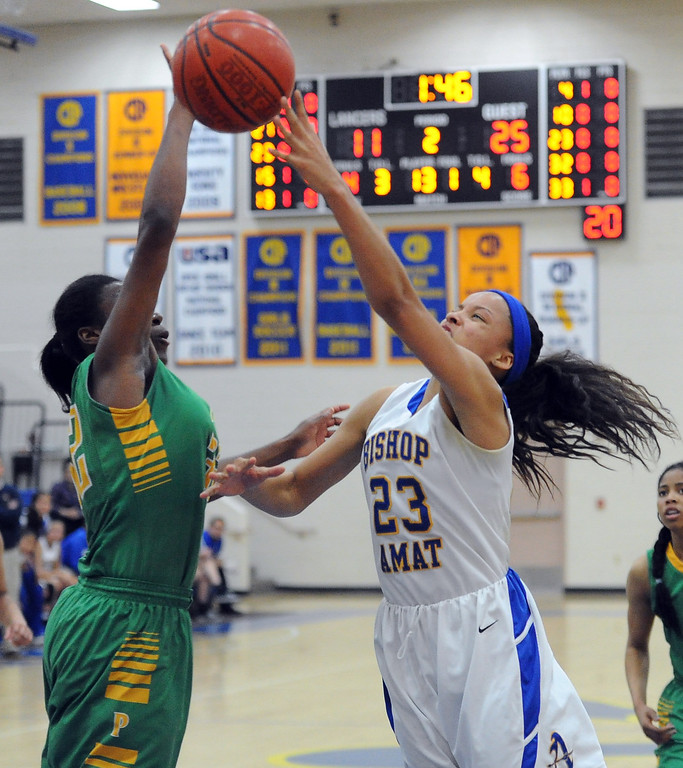 . Long Beach Poly\'s Jada Matthews (22) blocks the shot by Bishop Amat\'s Mauriana Clayton (23) in the first half of a CIF State Southern California Regional semifinal basketball game against Long Beach Poly at Bishop Amat High School on Tuesday, March 12, 2013 in La Puente, Calif. Long Beach Poly won 52-34.  (Keith Birmingham Pasadena Star-News)