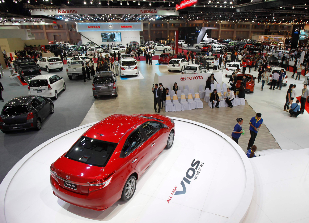 . Visitors gather around displays during a media presentation at the 34th Bangkok International Motor Show in Bangkok March 26, 2013. The Bangkok International Motor Show will be held from March 27 to April 7.  REUTERS/Chaiwat Subprasom