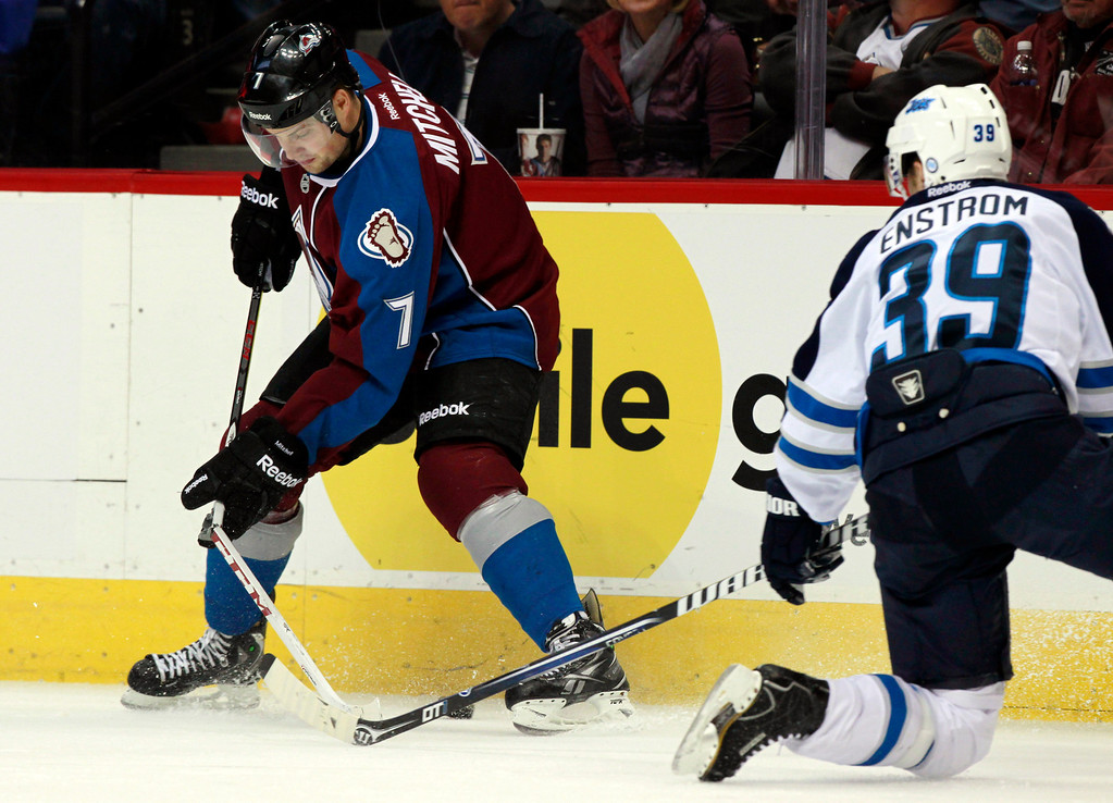 . Colorado Avalanche center John Mitchell, left, has his stick break while trying to clear the puck along the boards as Winnipeg Jets defenseman Tobias Enstrom, of Sweden, covers in the second period of an NHL hockey game in Denver on Sunday, Oct. 27, 2013. (AP Photo/David Zalubowski)
