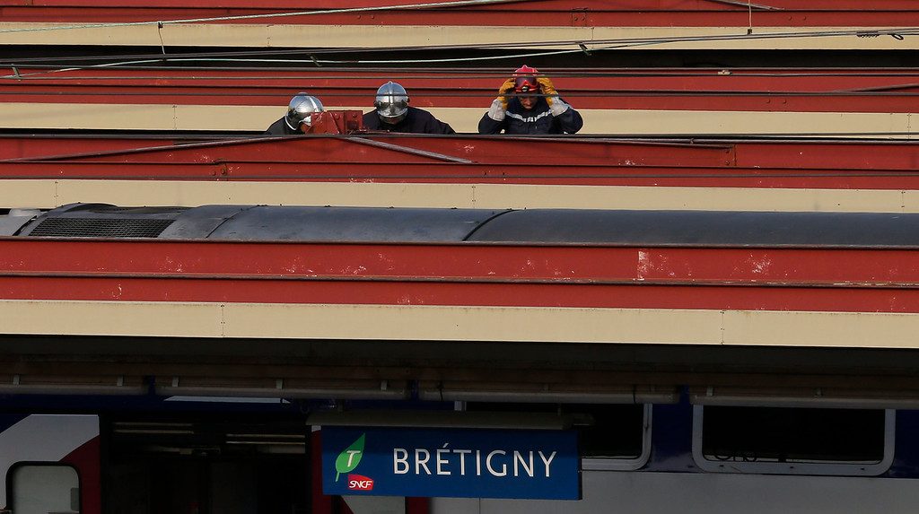 . Firefighters are seen on the roof of train after an intercity train accident at the Bretigny-sur-Orge station near Paris July 12, 2013.  REUTERS/Benoit Tessier