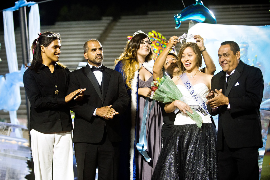 . Patrick Cordova, 16, a transgender senior, left, applauses with dad, Jose Cordova, after Ivory Gomez Gonzalez is crown Azusa High 2013 Homecoming Queen during halftime of the homecoming football game at Citrus College Stadium in Glendora on Friday night, Sept. 27, 2013. (Photo by Watchara Phomicinda/ San Gabriel Valley Tribune)