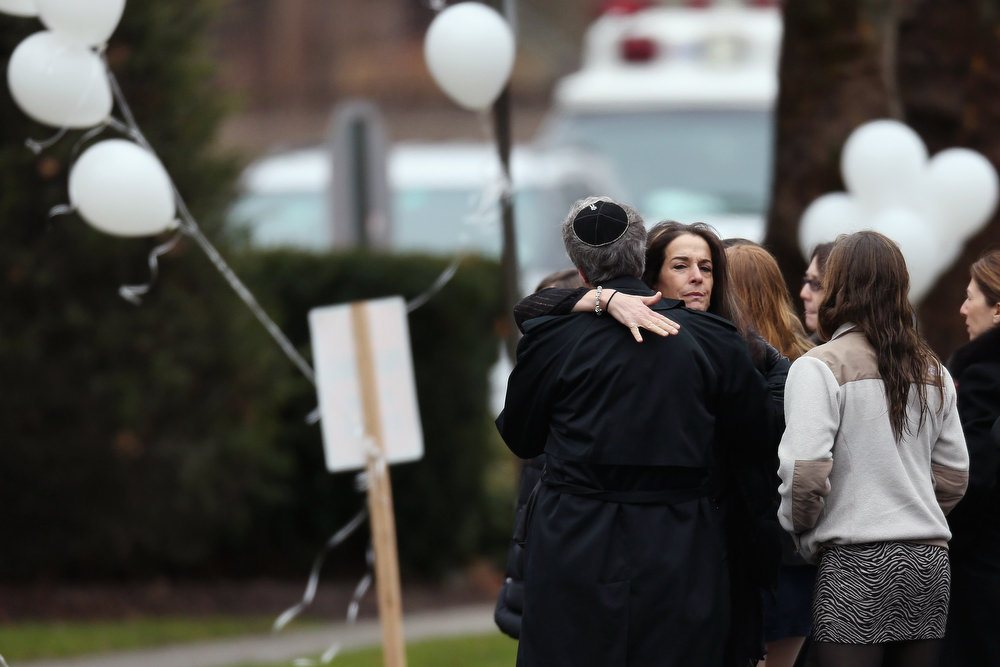 Description of . People embrace as they arrive for the funeral services of six year-old Noah Pozner, who was  killed in the shooting massacre in Newtown, CT, at Abraham L. Green and Son Funeral Home on December 17, 2012 in Fairfield, Connecticut. Today is the first day of funerals for some of the twenty children and seven adults who were killed by 20-year-old Adam Lanza on December 14, 2012.  (Photo by Spencer Platt/Getty Images)